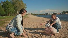 有他们的使用与在城市的水库的岸的沙子一起的女儿的年轻父母在期间 股票录像