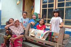 有他们的孩子的母亲在他们的房子前面在龙目岛,印度尼西亚 免版税库存图片