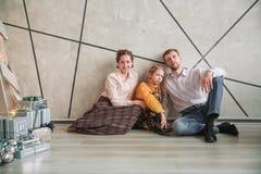 有他们的小女儿的父母坐在一栋新的公寓的地板 库存照片