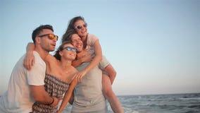 有他们的微笑和笑在海边的女朋友的两个英俊的大力士在刮风的天气期间在晚上 影视素材