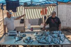 有他们的抓住的渔夫在一个室外市场上 免版税库存图片