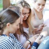 有他们的智能手机的女孩 库存照片