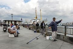有他们的标尺的渔夫在金黄垫铁附近在伊斯坦布尔 库存图片