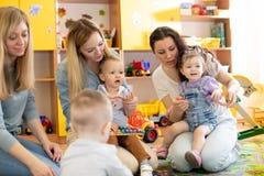 有他们的母亲的婴孩使用与玩具在托儿所 库存图片