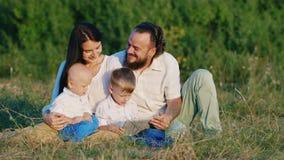有他们的父母的两个小兄弟在开花的草甸中的一种片剂使用 股票录像
