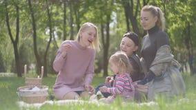 有他们的画象两年轻逗人喜爱的母亲孩子坐毯子在自然的绿色惊人的公园在春日 妈妈和 股票视频