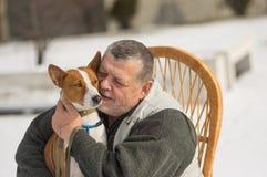 有他坐在藤椅的逗人喜爱的basenji狗的白种人老人晴朗的冬日 图库摄影