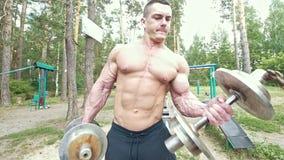 有他巨大的肌肉胳膊静脉的年轻人在森林里拾起重的哑铃 股票视频