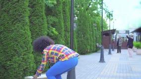 有他步行沿着向下有一个箱子的街道在他的手上并且投下它的一种非洲的发型的画象非裔美国人的妇女 股票录像