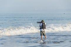 有他的专业照相机的年轻摄影师为小船照相的在海 免版税库存照片