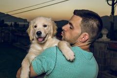 有他的人亲吻他的小狗的 库存图片