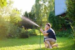 有他的使用与水管的父亲的滑稽的小男孩在晴朗的后院 获得学龄前儿童的孩子与水浪花的乐趣  免版税库存图片