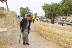 有他的做他的在橄榄山下的叫化子` s碗的一个年长人方式在市耶路撒冷以色列 免版税库存照片