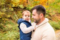 有他的儿子的年轻父亲在秋天森林里 免版税库存照片