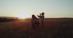 有他的儿子的爸爸在领域上面的惊人的日落的,拿着一架红色飞机,爸爸讲话与他的儿子和鼓励 影视素材