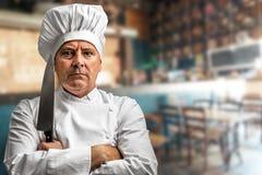 有他的刀子的疯狂的厨师 图库摄影
