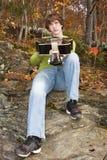 有他的吉他的一个年轻人在秋天森林 免版税库存照片