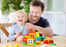 有他的在家使用与五颜六色的塑料块的父亲的小男孩 图库摄影