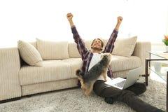 有他的坐在一个宽敞客厅的狗的愉快的人 免版税库存照片