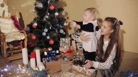 有他的姐妹的小男孩在美妙地装饰的圣诞树附近打开新年` s礼物盒 孩子是 影视素材