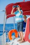 有他的姐妹的男孩上尉在船上在夏天巡航的航行游艇 旅行冒险,乘快艇与家庭的孩子 图库摄影