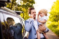 有他的小男孩和智能手机的年轻父亲在汽车 图库摄影