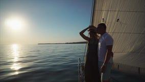 有他的年轻人优美的女朋友在游艇边缘站立有风帆的 股票录像