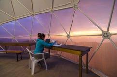 有他的文书工作的科学家在坐在前面的圆顶帐篷 免版税库存图片