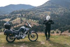 有他的旅游摩托车的骑自行车的人人,有大袋子的准备好一次长的旅行,黑样式,白色盔甲,乘驾,冒险,室外 免版税库存照片