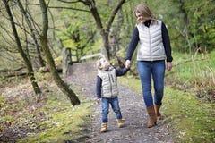 有他的母亲的可爱的小男孩在秋天公园 库存照片