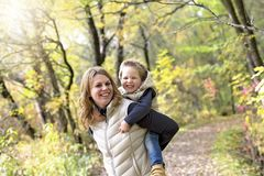 有他的母亲的可爱的小男孩在秋天公园 库存图片