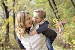 有他的母亲的可爱的小男孩在秋天公园 免版税库存照片