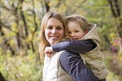 有他的母亲的可爱的小男孩在秋天公园 图库摄影