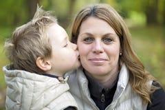 有他的母亲的可爱的小男孩在秋天公园 免版税库存图片
