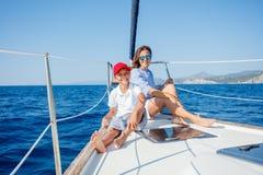 有他的母亲的男孩在船上在夏天巡航的航行游艇 库存照片