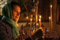 有他的点燃一个蜡烛的母亲的一个孩子在教会里 免版税库存图片