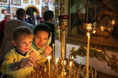有他的点燃一个蜡烛的母亲的一个孩子在教会里 库存图片