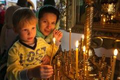 有他的点燃一个蜡烛的母亲的一个孩子在教会里 免版税库存照片