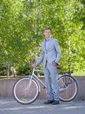 有他的白色自行车的一个人沿街道走反对绿色树背景  图库摄影