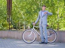 有他的白色自行车的一个人沿街道走反对绿色树背景  库存照片