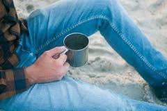 有他的看对海景的早晨咖啡的年轻人游人 免版税图库摄影
