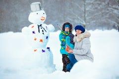有他的绘雪人的母亲的小男孩 免版税库存图片