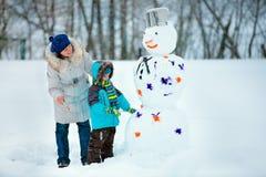 有他的绘雪人的母亲的小男孩 免版税库存照片