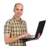 有他的膝上型计算机的微笑的年轻人 库存照片