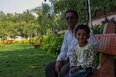 有他的花费愉快的质量时间的祖父的孙子在公园 免版税库存照片