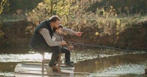 有他的花费美妙的时间的儿子的美丽的秋天天爸爸一起抓从湖的有些鱼 股票录像