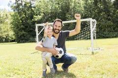有他的踢在橄榄球球场的小儿子的年轻父亲橄榄球 库存图片