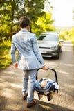 有他的进入汽车的小婴孩的年轻父亲 库存照片