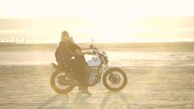 有他的骑一辆摩托车的女朋友的美丽的少妇摩托车骑士在沙漠在日落或日出 自行车的女朋友 股票录像