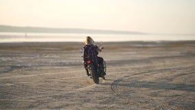 有他的骑一辆摩托车的女朋友的美丽的少妇摩托车骑士在沙漠在日落或日出 自行车的女朋友 股票视频
